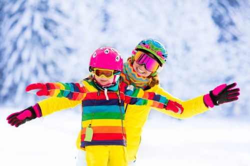 51422057 - mother and little child skiing in alps mountains. active mom and toddler kid with safety helmet, goggles and poles. ski lesson for young children. winter sport for family. little skier racing in snow